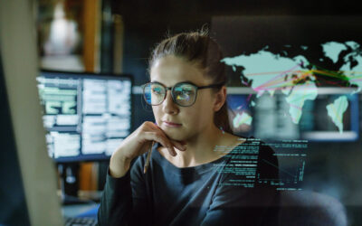 Stock image of a young woman, wearing glasses, surrounded by computer monitors in a dark office. In front of her there is a see-through displaying showing a map of the world with some data.